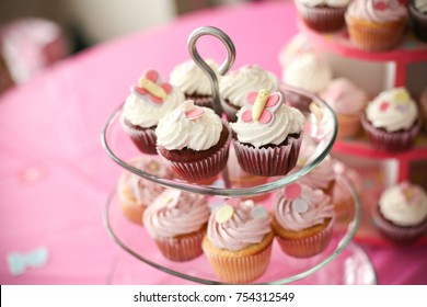 vanilla and chocolate gourmet cupcakes on a tiered glass display stand