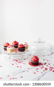 Vanilla and Chocolate Valentine Cupcakes on a Cake Plate with One Isolated on Heart-Shaped Doily in Front; Heart-Shaped Sprinkles on White Marble Countertop