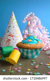 Vanilla cupcake with blue frosting and a birthday candle with hats and blower on a wooden table and a blue background