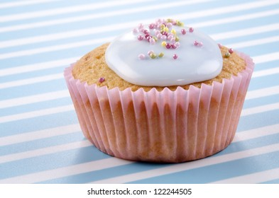 vanilla cupcake with bright blue icing and sprinkles