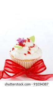 Vanilla cupcake with butter cream icing and leaves on white background