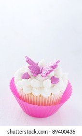 Vanilla cupcake with buttercream icing and butterfly decorations on white background