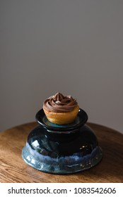 Vanilla cupcake with chocolate frosting on an isolated background.