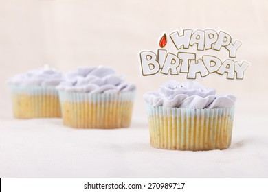vanilla cupcake frosting with buttercream, flower shape, decorated with happy birthday label
