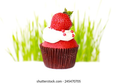 A vanilla cupcake with white frosting and a strawberry on top.