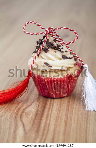 Vanilla cupcakes with 1 St of March red and white bow trinket  on wood