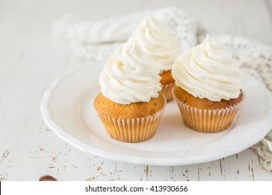 Vanilla cupcakes on white wood background, copy space