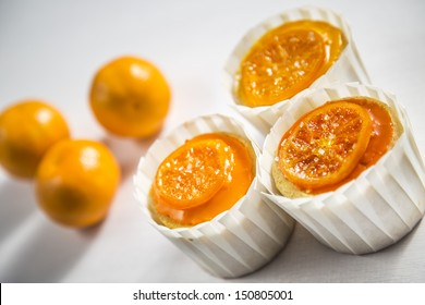 Vanilla Cupcakes With Orange Glaze and Candied Clementine in White Cupcake Wrappers on a White Wood Natural Background