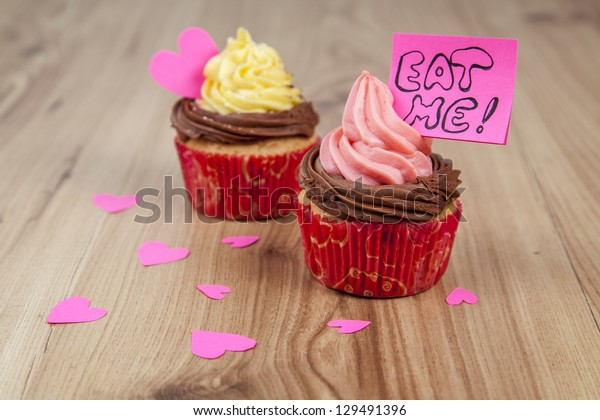 Vanilla cupcakes with pink hearts and eat me message on wood