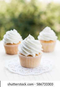 Vanilla cupcakes topped with swirl of white vanilla frosting captured on the wooden table in a sunny day.