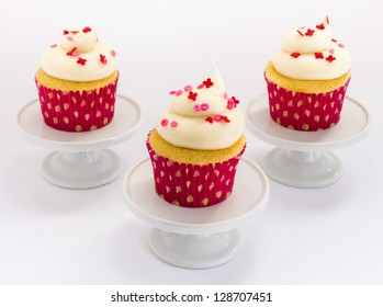 Vanilla cupcakes with white frosting and xoxo sprinkles on pedestals