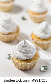 Vanilla cupcakes white white whipped cream on a white table