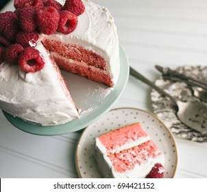 Vanilla frosted raspberry cake with a slice plated and ready to eat.