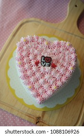 Vanilla heart cake with pink butter cream on wooden plate