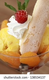 vanilla ice cream with cream, berries, apricots and sweet biscuit, close up