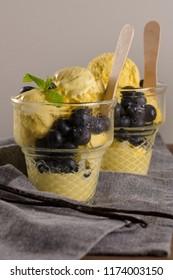 Vanilla ice cream with blackberries in the glass vases.