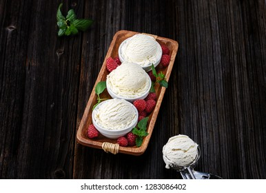 Vanilla ice cream with bowl and berries on wooden background