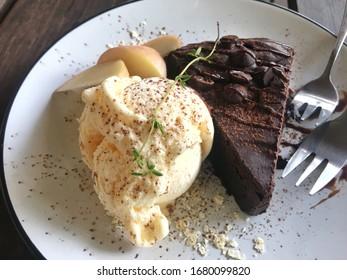 Vanilla ice cream with brownie chocolate cake on white dish