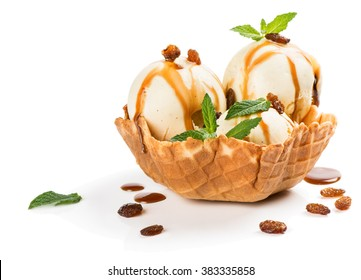 Vanilla ice cream with caramel sauce, raisins and mint in a wafer bowl isolated on white background