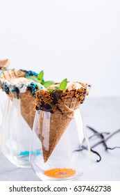Vanilla  ice cream with caramel sauce in waffle cone decorated with dark chocolate and sprinkles served in glass on light gray table