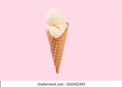 Vanilla ice cream cone on pink faded pastel color background. Vanilla ice cream in wafer cup.
