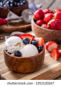 Vanilla ice cream with fresh blueberries and strawberries in a wooden bowl with bowls of berries in background