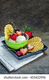 Vanilla ice cream scoops with fresh berries fruit
