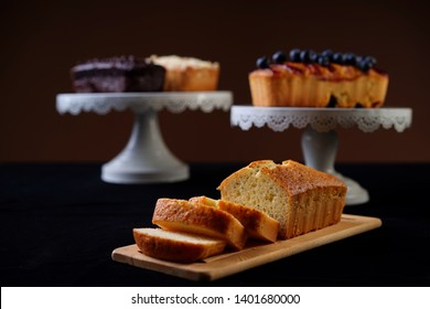 Vanilla loaf cake slices on a brown cutting board with chocolate, blueberry and apple loaf cakes on cake stands at the back. Selective focusing. Dark food photography.