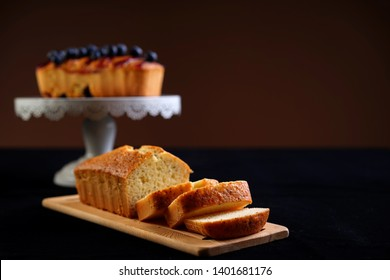 Vanilla loaf cake slices on a brown cutting board with blueberry loaf cake on cake stand at the back. Selective focusing. Dark food photography.