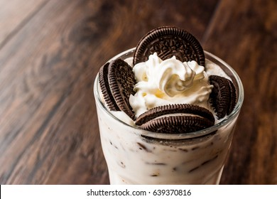 Vanilla Milkshake with chocolate cookies and black straw.
