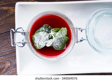 Vanilla panna cotta with strawberry sauce and mint isolated on black