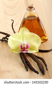 Vanilla pods, flower and bottle on a wooden background