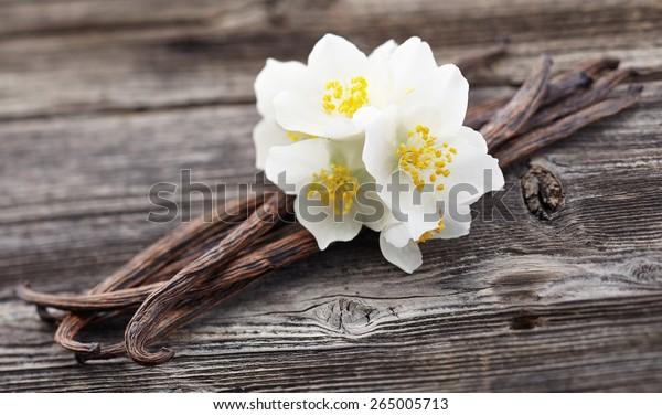 Vanilla pods with jasmine on a wooden background