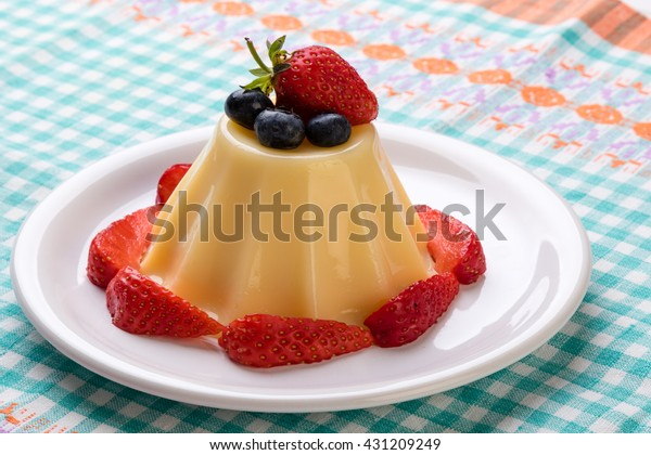 vanilla pudding on white plate with fruits