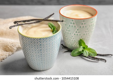 Vanilla pudding, sticks and fresh mint on table
