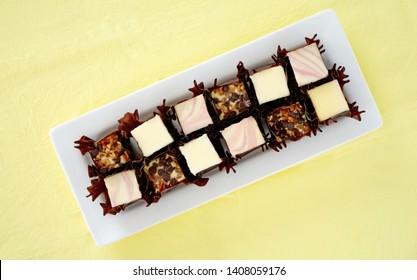 Vanilla, raspberry swirl and walnut chocolate chip mini cheesecake bites in dark wrappers on long white plate on yellow fabric background.