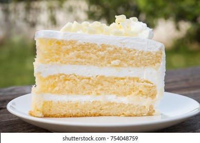 Vanilla sponge cake with cream and white chocolate decorate. Sliced piece of cake on white plate. Served on wooden table. Favorite dessert for celebrate event or birthday party.