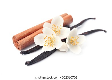 Vanilla sticks and cinnamon with flowers on white backgrounds.