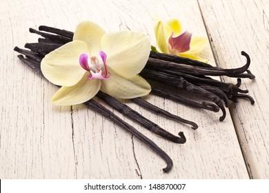 Vanilla sticks with vanilla flower on a white wooden table.