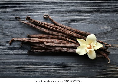 Vanilla sticks and flower on wooden background