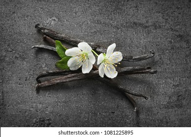 Vanilla sticks and flowers on grey background
