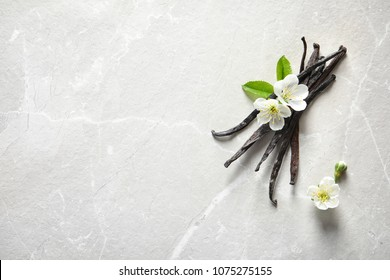 Vanilla sticks and flowers on light background