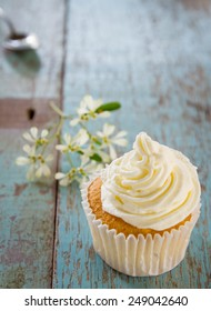 vanilla sweet cupcake with italian butter cream put on old wood table  with spoon