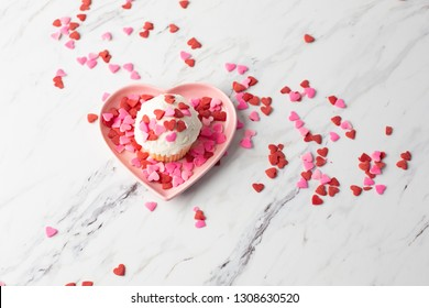 Vanilla Valentine Cupcake with White Frosting and Heart-Shaped Sprinkles on Pink Heart-shaped Dish; Sprinkles scattered on Marble Countertop