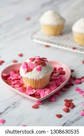 Vanilla Valentine Cupcake with White Frosting and Heart-Shaped Sprinkles on Pink Heart-shaped Dish; Sprinkles scattered on Marble Countertop; Undecorated Cupcakes on Wire Rack in Background