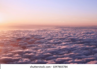 Vanilla vintage colored light sunset sky with fluffy clouds background. Sunset sky view from an airplane window.  Above the clouds