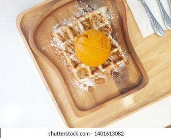 Vanilla Waffles on wooden trays. topping ice cream (Tea flavor).Sprinkle with icing sugar(powdered sugar).With a spoon placed beside the dessert.At the cafe