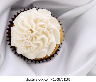 Vanilla wedding cupcake with buttercream white frosting with pearl sprinkles on a white tablecloth