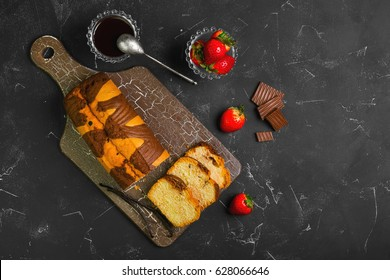 Vanilla-chocolate cut into pieces rectangular biscuit cake pie. Ingredients for biscuit cake are strawberry berries, chocolate sauce, vanilla pods, chocolate pieces. Dark black background. Top view.