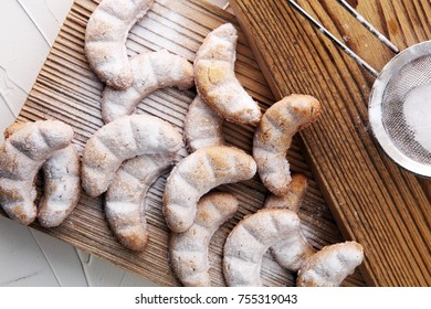 Vanille Kipferl cookies for christmas on brown wood with sugar.